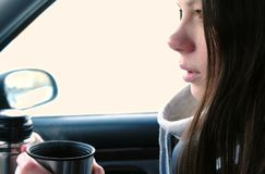 Young brunette woman drinks tea from a thermos sitting in a car in the winter. stock images