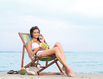 A young brunette woman eating fruits and relaxing on the beach Stock Photo