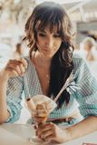 Young brunette woman eating a glass of ice cream stock images