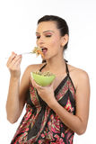 Young brunette woman eating noodles. In the green bowl Stock Photo