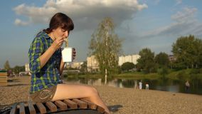 Young woman eats instant noodles from box on deck chair. Young brunette woman eats instant noodles from white box using chopsticks, girl in blue checkered shirt stock footage