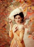 A young brunette woman with an elegant, hairstyle in a hat with a strass feathers. Lady in a yellow vintage dress walks through th royalty free stock image