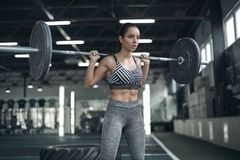 Young woman exercises in gym healthy lifestyle ready to lift barbell Royalty Free Stock Photography