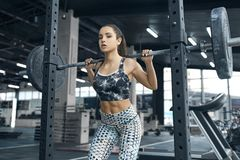 Young woman exercises in gym healthy lifestyle pulling weights Stock Photography