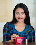 Young brunette woman facing camera, holding piggy bank and placing money inside it, smiling happily Royalty Free Stock Photos