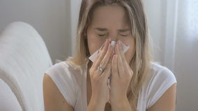 Young brunette woman feeling caught flu sitting on sofa and sneezing in paper tissue. Footage shot in 4K stock video footage