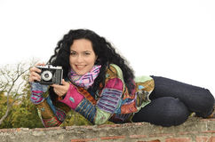 Young brunette woman with fhoto camera. Brunette beautiful woman with photo camera taking pictures outdoor, dressed in hippie costume Stock Image