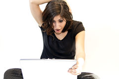 Young Brunette Woman Finds Surprise on Computer. A young brunette woman finds a welcome surprise on her notebook computer stock photo