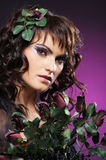 A young brunette woman in flowers and beautiful makeup. A young and attractive brunette Caucasian woman posing in beautiful flowers and makeup. The image is Stock Images