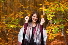 Young brunette woman in forest holding leaves stock photo