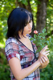 Young brunette woman in the garden with the little rose Royalty Free Stock Photos