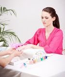 Young brunette woman get manicure in salon Stock Photo