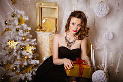 Young brunette woman with gift near Christmas tree Royalty Free Stock Photography