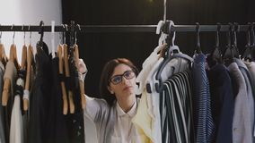 Young brunette woman in glasses looking through a rail of clothing on hangers. Young caucasian woman choosing clothes on. A rack in a showroom, 4k stock video footage