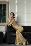 Young brunette woman in gold dress on sofa Stock Images