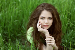 Young brunette woman on the green field grass, outdoors portrait Royalty Free Stock Photos