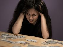 Young Brunette Woman Grieves in Desperation because She Lost All Her Money on Playing Cards. royalty free stock photos