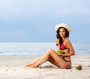 A young brunette woman in a hat eating fresh grapes Royalty Free Stock Images