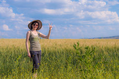 Young brunette woman with hat making peace sign in a field. Peace concept. Royalty Free Stock Images