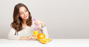 Young brunette woman having orange juice. Royalty Free Stock Photo