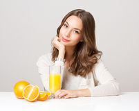 Young brunette woman having orange juice. Stock Image