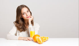 Young brunette woman having orange juice. Royalty Free Stock Photos