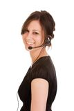 Young brunette woman with headset. Young friendly brunette woman with headset smiling during conversation Royalty Free Stock Photography