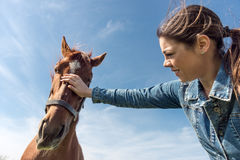 Young brunette woman and her horse Royalty Free Stock Photo