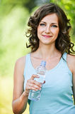 Young brunette woman holding bottle. Portrait of young pretty brunette curly woman wearing blue t-shirt, holding bottle of water at summer green park Royalty Free Stock Photo