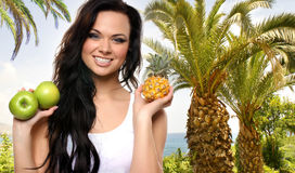 A young brunette woman holding fresh fruits Royalty Free Stock Images