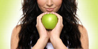 A young brunette woman holding a fresh green apple. Portrait of a young and attractive brunette Caucasian woman holding a fresh green apple. The image is taken Royalty Free Stock Images