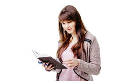 Young brunette woman holding a notebook and pen on white isolated background Royalty Free Stock Image