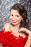 A young brunette woman holding red feathers Royalty Free Stock Images