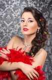 A young brunette woman holding red feathers Stock Photography