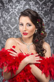 A young brunette woman holding red feathers Stock Photo