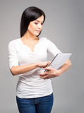 Young brunette woman holding a tablet computer on grey Stock Images