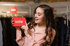 Young brunette woman holds red sign with sale word royalty free stock photo