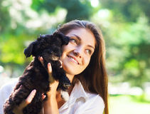 Young brunette woman hugging her lap dog puppy Stock Photography