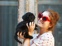 Young brunette woman hugging her lap dog puppy Stock Image