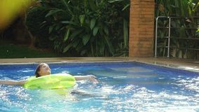 Young brunette woman with an inflatable circle has a happy time in swimming pool in slow motion. 1920x1080 stock video footage