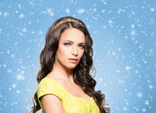 Young brunette woman in jewelry and a white dress. Beautiful brunette with luxury golden necklace over blue winter background. Christmas concept Royalty Free Stock Photos