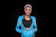Young brunette woman in jogging clothes after sportive exercise. Isolated on black (colored, retouched royalty free stock images