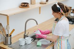 Young brunette woman in a kitchen is washing cups and dishes royalty free stock photography