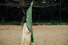 Young brunette woman with a large leaf exotic palm tree. Girl covered face with a large leaf tropical palm tree. Girl covered face with a large leaf exotic stock photography