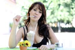 Young brunette woman licks ice cream from a spoon Royalty Free Stock Photography