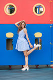 Young brunette woman in light striped white blue dress having fun at playground outdoor Royalty Free Stock Photography