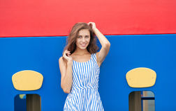 Young brunette woman in light striped white blue dress having fun at playground outdoor Stock Photography