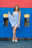 Young brunette woman in light striped white blue dress having fun at playground outdoor playing with her dress Royalty Free Stock Photography