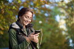 Young brunette woman listening to music in autumn park. Stock Images