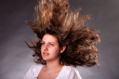 Young brunette woman with long flying hair Stock Images